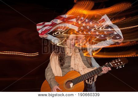 Girls celebrate Independence Day at night. Singer with guitar and happy girl with flying american flag on blurred city lights background. Youth lifestyle concept