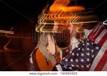 Friends celebrate Independence Day at night. Singer with guitar and happy girl with american flag on blurred city lights background. Youth lifestyle concept