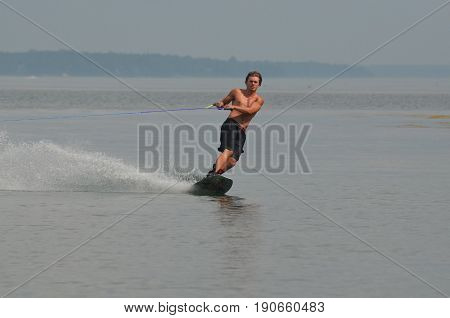 Young guy riding a wakeboard in Maine's Casco Bay on a summer day.