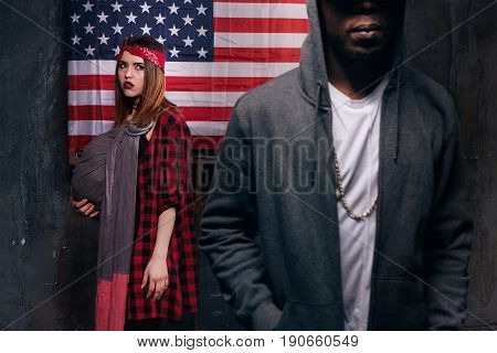Divorce in american family. Angry wife. Black man and caucasian woman with little baby on US national flag background. Social problem, child custody, youth pregnancy concept