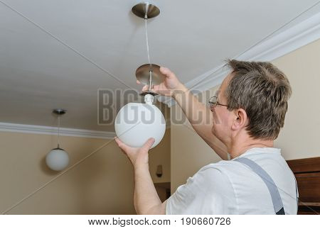 Electrician is instilling a ceiling lamp with led bulb.