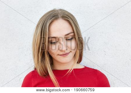Sensual woman with fair hair and beautiful face looking down thoughtfully having some dreams in her mind while posing in white studio. Pensive woman with beautiful appealing appearance in red clothes