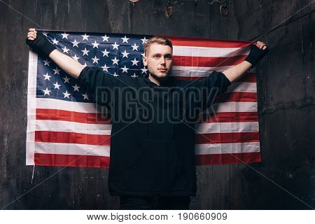 Young man with USA national flag in studio. Strong guy in black cloth with stars and stripes behind him. Independence day, confidence, pride, fidelity to the nation, memorial day concept