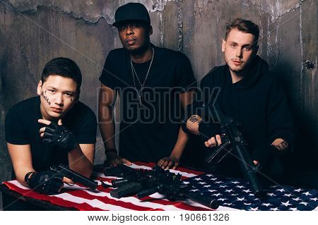 American gangs with weapons. Interracial young people with tattoos hold guns and rifles in their hands. Outlaw, ghetto, murderer, armed attack concept