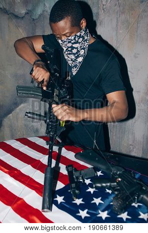 Black warrior is cleaning his rifle. Mercenary man with weapon in hand on dark gray background. Outlaw, ghetto, patriotic war, armed attack concept