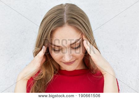 Indoor shot of tired fair-haired woman in red sweater holding her hands on temples having headache after hard work looking down. Woman wanting to remember some details having pensive look down