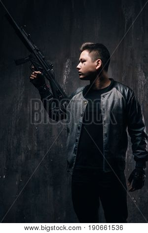 Tattooed killer with sniper rifle in black cloth, studio shoot. Armed white gangster man with weapon and tattoo on dark background. Outlaw, ghetto, murderer, robbery concept