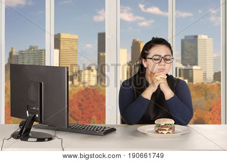 Hesitated businessman tries to diet while looking at the temptation of foods with the computer on the desk
