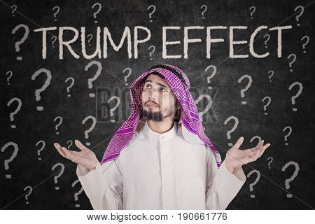 Arabian businessman looks confused with Trump Effect word and question marks on the background