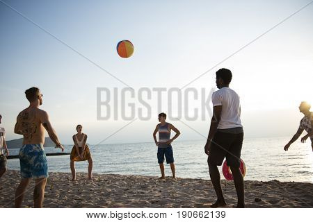 Group of diverse friends playing beach ball together