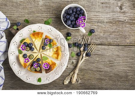 Homemade fresh cheesecake with blueberries and edible flowers on a white ceramic plate, on a simple wooden background. From the top view. The concept is helpful comfortable food.