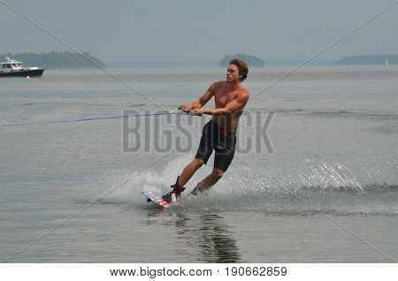 Summer in Casco Bay with a young guy wakeboarding.