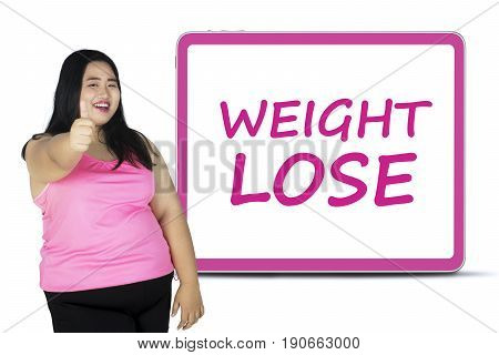 Overweight woman showing thumb up while standing with a text of weight lose on the board