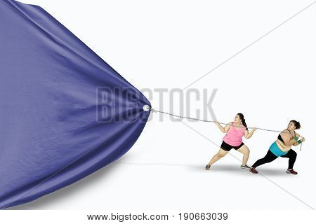 Two fat women wearing sportswear and using a chain to drag a big empty flag isolated on white background