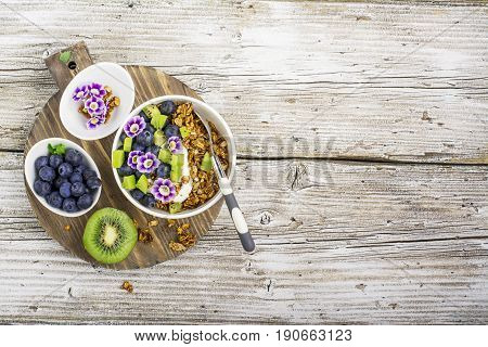 Healthy Breakfast: homemade roasted granola with blueberries, kiwi fruit and edible flowers on wooden background. From the top view. The concept of fitness nutrition.