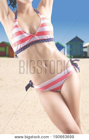 Summer Concept. Female model with beautiful body standing and posing on the beach while wearing striped swimsuit. Shot with beach huts background