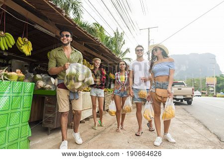 Woman Hold Bananas And Pineapple On Street Traditional Market, Young Man And Woman Travelers Buying Fresh Fruits