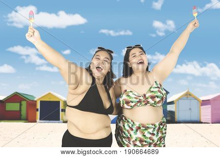 Summer holiday concept. Two joyful overweight women wearing bikini and holding ice cream while smiling happy on the beach