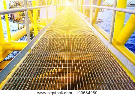 Bridge and handrail with grating on offshore platform with lighting in evening.
