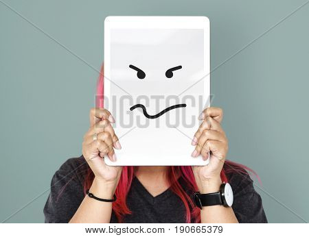 Woman holding digital tablet with moody face cover her face