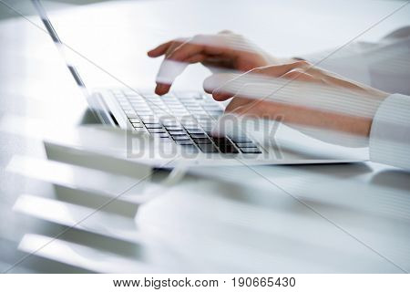 Close-up of hands of business man typing on a laptop. View through blinds
