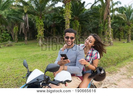 Couple Riding Motorbike, Young Man And Woman Using Cell Smart Phone Travel On Bike On Tropical Forest Road During Exotic Summer Holiday
