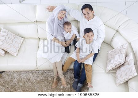 High angle of muslim family enjoying their togetherness while sitting on the sofa
