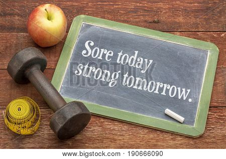 Sore today, strong tomorrow fitness concept  -  slate blackboard sign against weathered red painted barn wood with a dumbbell, apple and tape measure