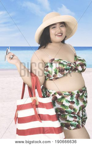 Summer holiday concept. Overweight young woman smiling on the beach while wearing swimsuit hat and carrying a summer bag