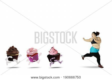 Diet concept. Overweight woman refusing to eat sweet foods to lose weight and run away from cupcakes isolated on white background