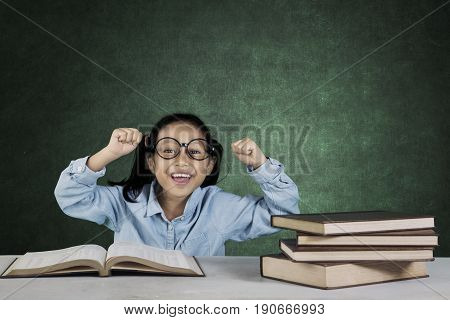 Portrait of smiling girl lifting hands while sitting in front of her book on the table in classroom