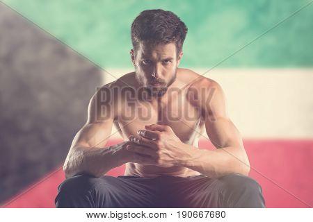 Muscular man with Kuwait Flag behind. Muscular man.
