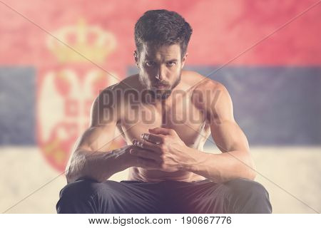 Muscular man with Serbian Flag behind. Muscular man.
