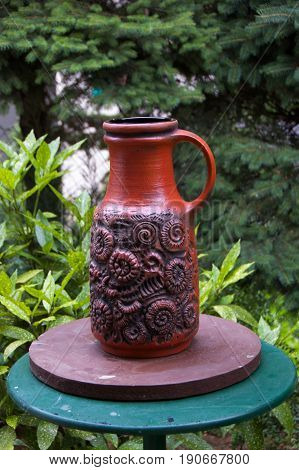 Decorative amphora on the table in the garden
