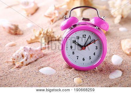 Pink alarm clock with seashells on beach sand