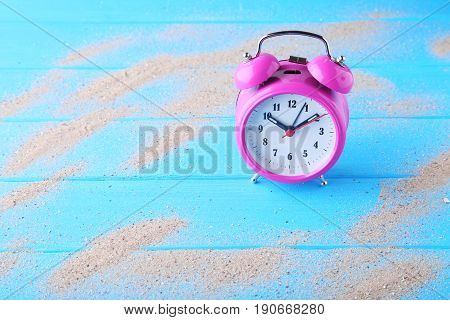 Pink alarm clock with beach sand on blue wooden table