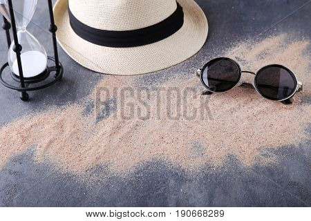 Hourglass With Beach Hat And Sunglasses On Grey Wooden Table