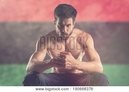 Muscular man with Libya Flag behind. Muscular man.