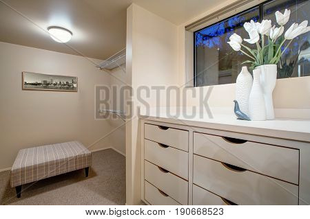 Narrow Walk-in Closet Features Built-in Drawers