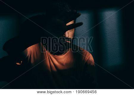 Prisoner Man In Dark Cell Hiding Face With Shame