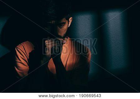 Prisoner Man In Dark Cell Depressed Or Praying