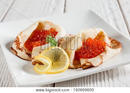 Dessert pancakes with red caviar on white plate. Russian traditional salty crepes with seafood. Shrove tuesday holiday food