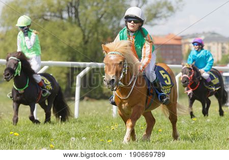 STOCKHOLM SWEDEN - JUNE 06 2017: Three young jockey girls riding cute ponys at Nationaldags Galoppen at Gardet. June 6 2017 in Stockholm Sweden