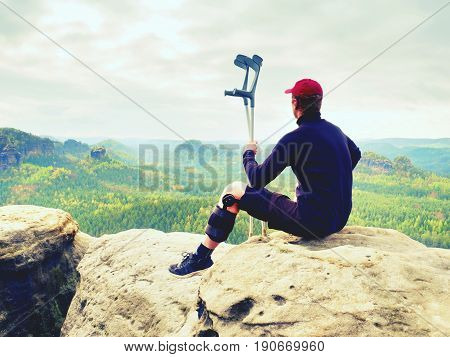 Tired Hurt Tourist With Medicine Crutches. Man With  Broken Leg In Knee Brace Features Resting On  E