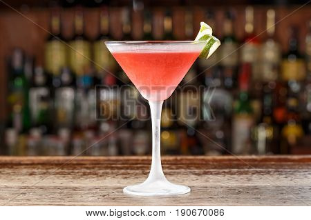 A cosmopolitan alcoholic cocktail is on the bar in a restaurant or in a club. Blurred background of alcohol.