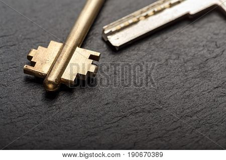 Bunch of golden metal keys on a black background horizontal photo