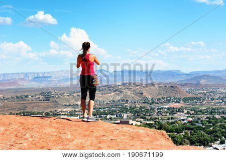 Woman atop the Sugarloaf rock formation overlooking St George, Utah.
