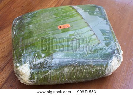 Large block of fresh Mexican cheese wrapped in banana leaf for sale in Chiapas Mexico