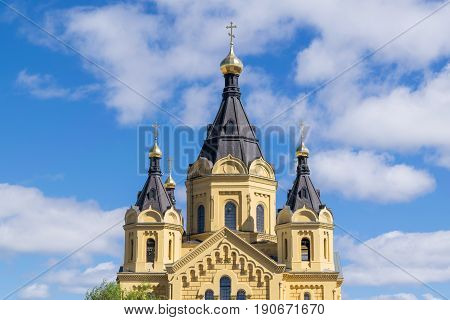 The upper part of the Orthodox Church of Alexander Nevsky on the background of blue sky with Cumulus clouds on a Sunny day. Views of the front side of the temple.