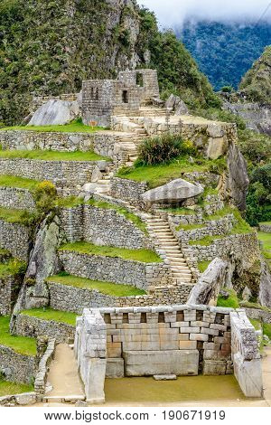 Sacred plaza and the hill with intiwatana observatory rock at ancient incas town of Machu Picchu, Peru